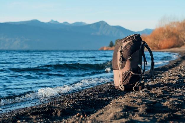 Plecak podróżnika na ziemi w pobliżu jeziora.