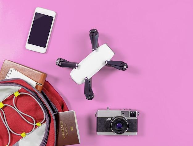 Plecak podróżny z akcesoriami podróżnymi na różowym tle
