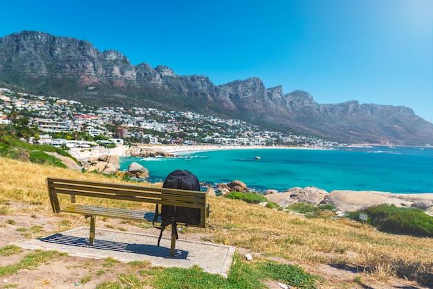 Plecak samotnego podróżnika na ławce z widokiem na camps bay piękną plażę w cape town, republika południowej afryki