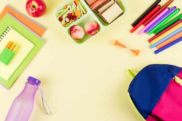Plecak, szkolne pudełko śniadaniowe i artykuły papiernicze na pastelowym pulpicie, miejsce na kopię