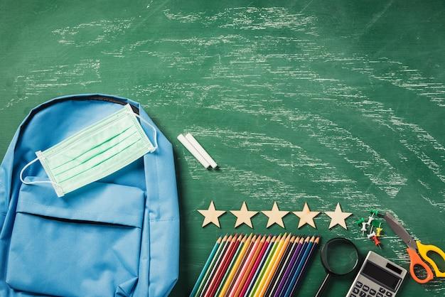 Plecak szkolny na zielonej tablicy z ochroną maski