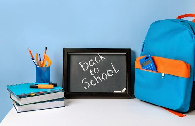Plecak szkolny z kolorowymi przyborami szkolnymi i tablicą z napisami powrót do szkoły. przybory szkolne na niebieskim tle. projekt banera