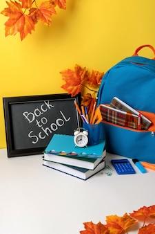 Plecak szkolny z kolorowymi przyborami szkolnymi i tablicą z napisami powrót do szkoły. przybory szkolne na żółtym tle. projekt banera