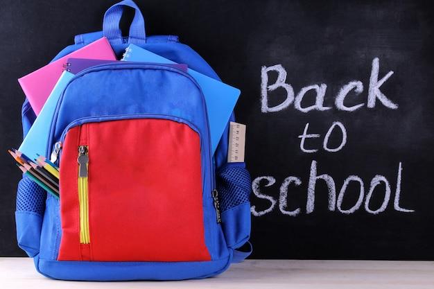 Plecak szkolny z przyborami szkolnymi na tle tablicy szkolnej