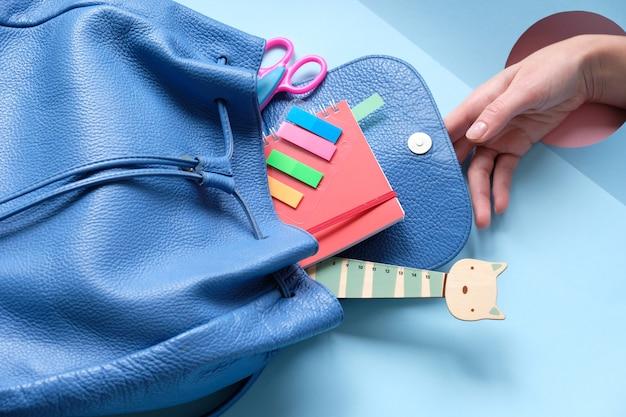 Plecak z różnymi kolorowymi artykułami na stole.