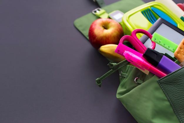 Plecak z szkolnymi dostawami na czarnym tle.