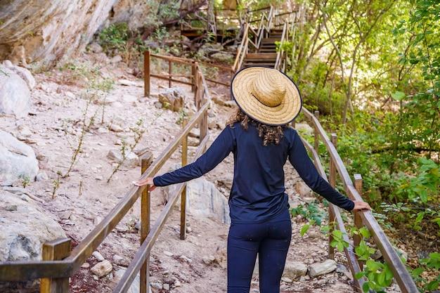 Plecami do siebie młoda kobieta podróżująca na szlaku. podróżująca kobieta. wycieczka