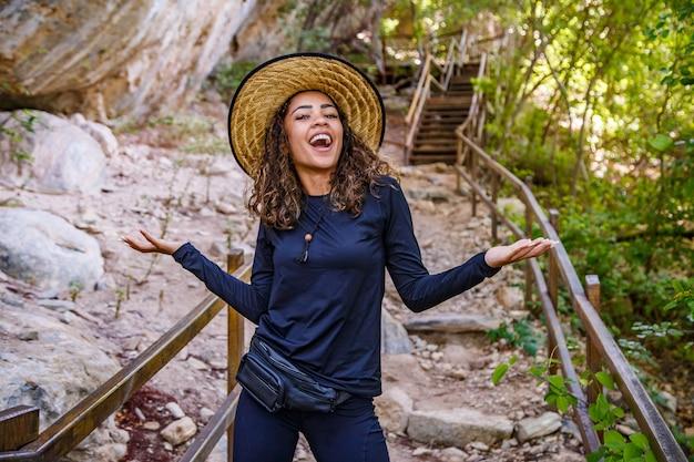Plecami do siebie młoda kobieta podróżująca szlakiem uśmiechnięta patrząc na kamerę