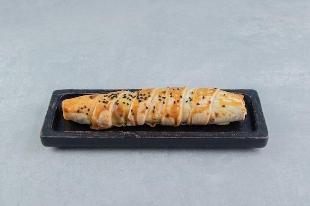Pleciona bułka nadziewana mięsem na czarnym talerzu.