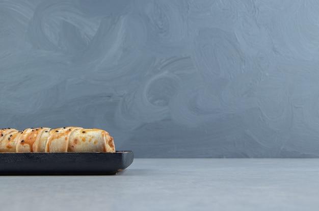Pleciona bułka z sezamem na czarnym talerzu.
