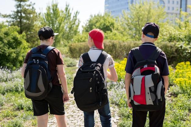 Plecy dzieciaków z kolorowymi plecakami
