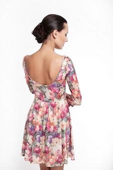 Plecy młoda piękna kobieta w kolorowej lato sukni odizolowywającej na bielu