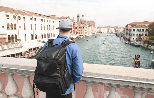 Plecy młodego turysty z czarnym plecakiem