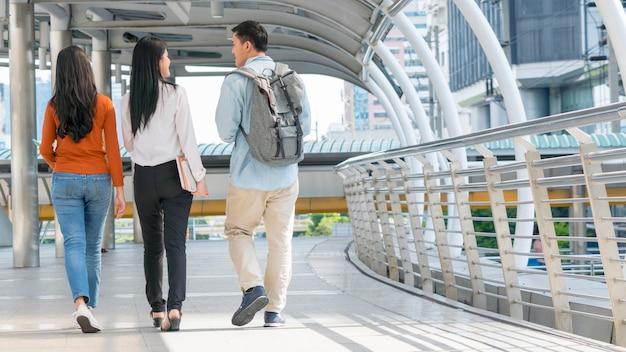 Plecy nastolatków i kobiety biznesu chodzą i rozmawiają