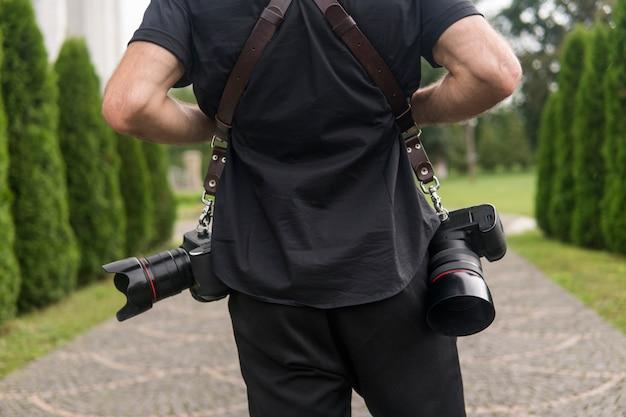 Plecy profesjonalnego fotografa w czarnej koszuli z dwoma aparatami i ramiączkami na tle zielonego ogrodu.