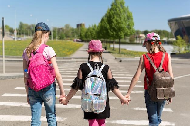 Plecy uczniów z kolorowymi plecakami poruszającymi się po ulicy