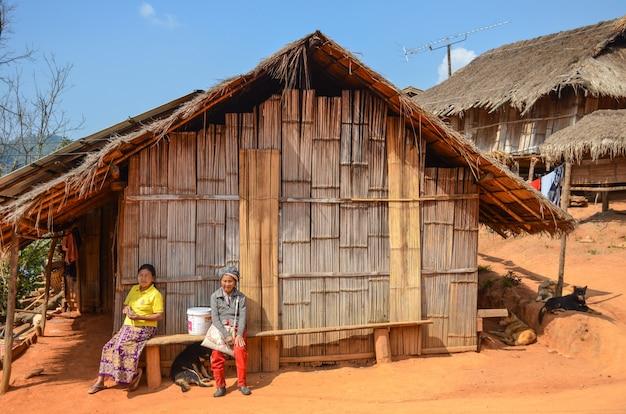 Plemienna kobieta siedzi przed ich domem
