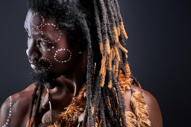 Plemienny mężczyzna z dredami patrząc z boku, w kontemplacji, myślący o czymś odosobnionym