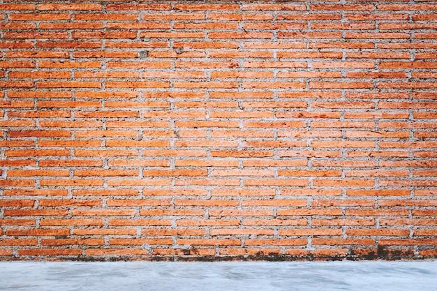 Plenerowa betonowa podłogowa tekstura z czerwonych cegieł ściany tłem.