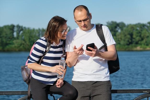 Plenerowa dojrzała para używa smartphone