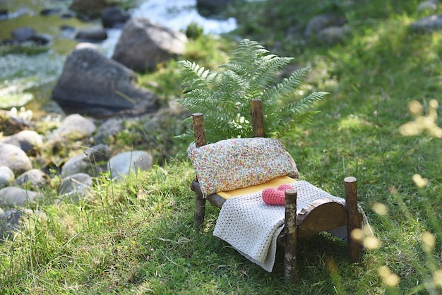 Plenerowa fotografia noworodkowa z drewnianym łóżkiem w przyrodzie z paprociami.