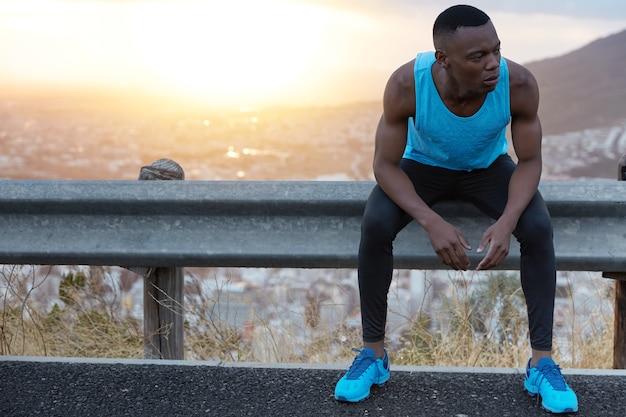 Plenerowe ujęcie mężczyzny o sprawnej sylwetce, dbającego o zdrowie, zamyślonego odwracającego wzrok, odpoczywającego po treningu, podziwiającego wschód słońca z miejscem na tekst reklamowy lub promocyjny