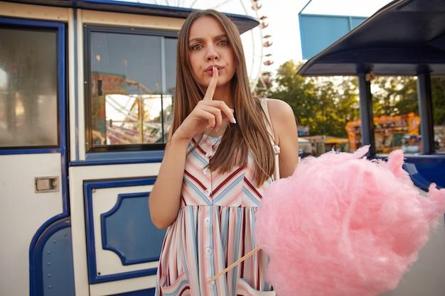 Plenerowe ujęcie młodej długowłosej brunetki w lekkiej letniej sukience stojącej nad parkiem rozrywki z watą cukrową w dłoni, patrzącej z poważną miną i unoszącym palec wskazujący w geście uciszenia