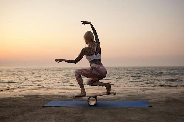 Plenerowe ujęcie młodej wytatuowanej kobiety o dobrej sylwetce, pozującej nad widokiem na morze, noszącej sportowe ubrania, próbującej utrzymać równowagę na specjalnym sprzęcie sportowym z podniesionymi rękami