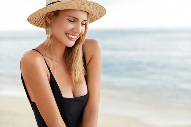 Plenerowe ujęcie pięknej, uśmiechniętej młodej kobiety w letnim ubraniu, nieśmiało i pozytywnie wyglądającej, odtwarza się na plaży w upalny letni dzień, uśmiecha się radośnie, zadowolona z dobrego wypoczynku. styl życia