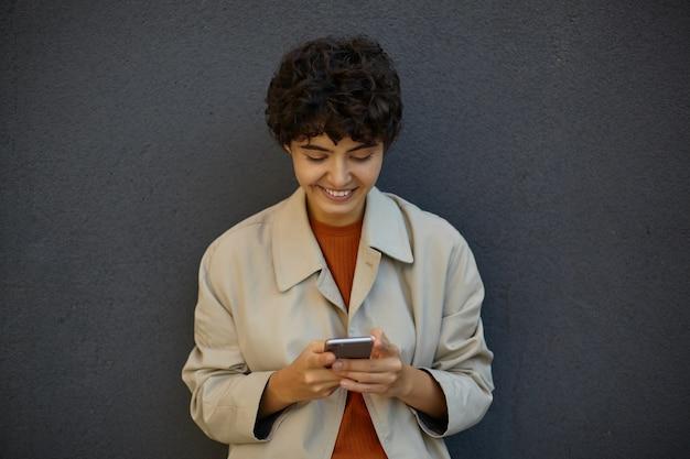 Plenerowe ujęcie przyjemnie wyglądającej młodej ciemnowłosej kobiety z krótką fryzurą trzymającą telefon komórkowy w uniesionych rękach i uśmiechającą się wesoło, pozując na czarnej ścianie miejskiej w stylowych ubraniach