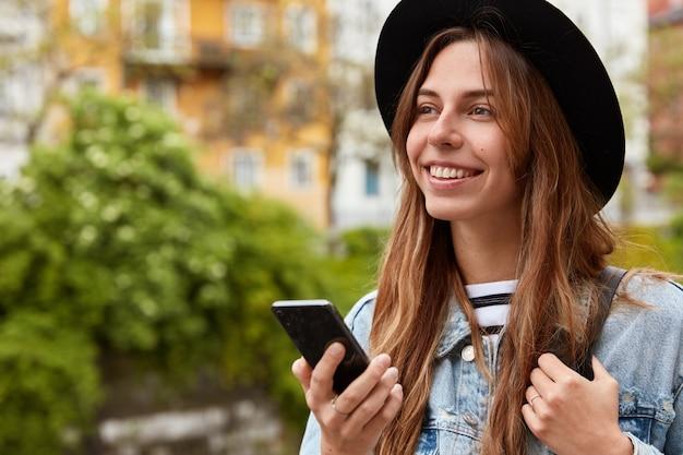 Plenerowe ujęcie rozmarzonej europejskiej kobiety w sieciach społecznościowych, spacery po mieście nad zieloną plantacją, z pozytywnym uśmiechem na twarzy