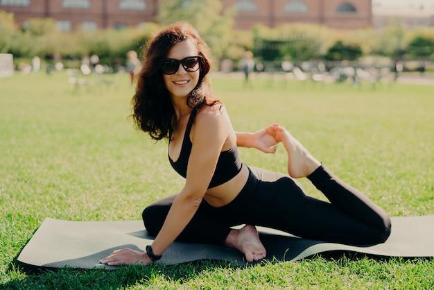 Plenerowe ujęcie sportowej uśmiechniętej kobiety rozciąga nogi na karemacie, uśmiecha się pozytywnie nosi odzież sportową, ma trening fitness dla elastyczności, wykonuje ćwiczenia rozciągające, cieszy się świeżym powietrzem i zielonym trawnikiem.
