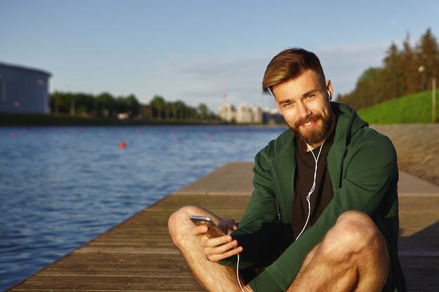 Plenerowe ujęcie wesołego przystojnego młodego europejczyka z rozmytą brodą i stylową fryzurą, słuchającego muzyki nad rzeką, używającego ucha i odtwarzacza mp3, patrzącego z szerokim, szczęśliwym uśmiechem