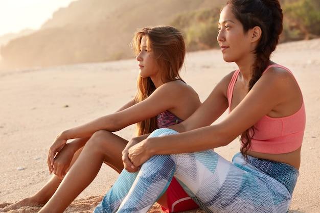 Plenerowe ujęcie zamyślonych kobiet odpoczywających po treningu cardio na wybrzeżu