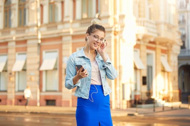 Plenerowe zdjęcie blondynki młodej kobiety w okularach spaceruje po mieście ubrana niedbale w dżinsową kurtkę i obcisłą niebieską spódnicę