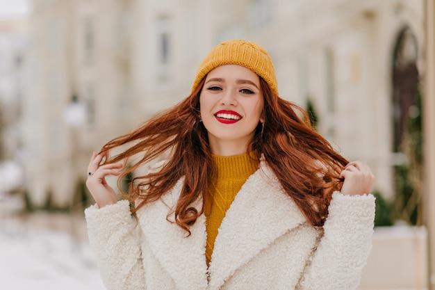 Plenerowe zdjęcie niesamowitej rudowłosej kobiety tańczącej na ulicy. wesoła ruda pani śmiejąca się w zimny dzień.