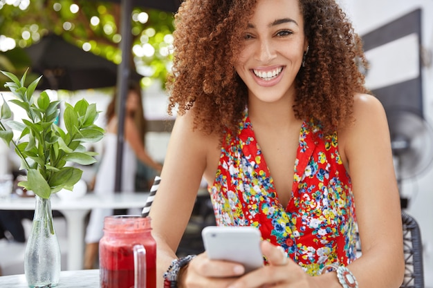 Plenerowe zdjęcie pięknej kręconej kobiety o ciemnej skórze, czyta przyjemne wiadomości lub wyszukuje informacje w sieciach społecznościowych