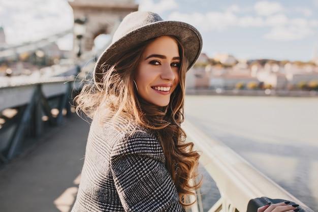 Plenerowe zdjęcie romantycznej europejki z kręconymi fryzurami spędzającej czas na świeżym powietrzu, zwiedzając europejskie miasto