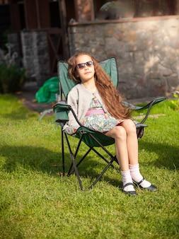 Plenerowe zdjęcie słodkiej dziewczyny opalającej się na krześle na trawie