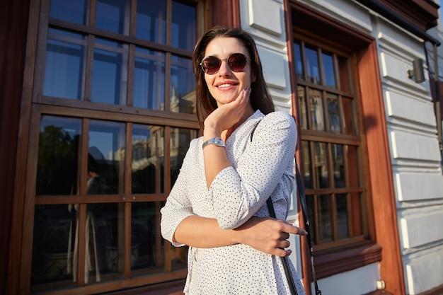 Plenerowe zdjęcie wesołej, ładnej, młodej, długowłosej brunetki kobiety w okularach przeciwsłonecznych idącej ulicą w ciepły słoneczny dzień, opierając brodę na uniesionej ręce i szeroko uśmiechając się