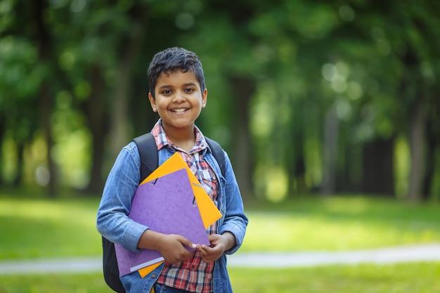 Plenerowego portreta afro amerykańska szczęśliwa szkolna chłopiec z książkami i plecakiem. młody student zaczyna zajęcia po wakacjach. powrót do koncepcji szkoły.