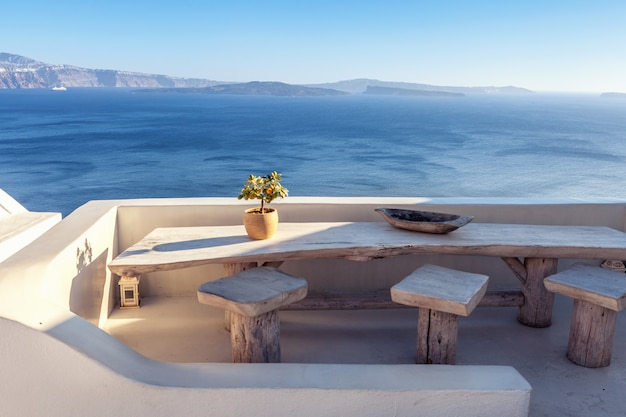 Plenerowy domu taras z drewnianym rocznika stołem z dennym widokiem w santorini, grecja.
