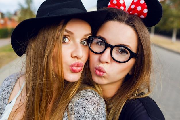 Plenerowy ładny portret najlepszych przyjaciółek pięknych dziewczyn, zabawy razem, uśmiechnięty, emocje, fajny wiosenny strój, jasne kolory, białe zęby.