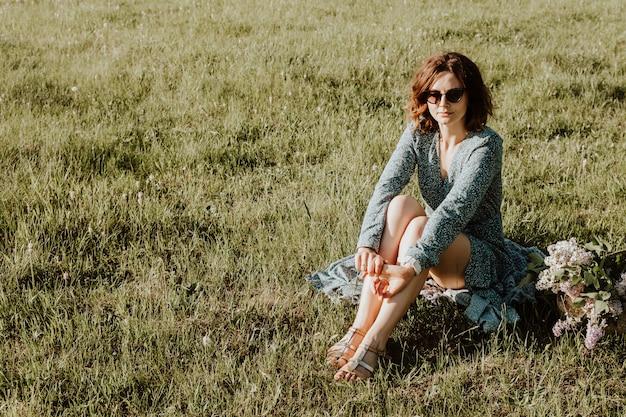 Plenerowy moda portret piękna młoda kobieta w bławej sukni i okularach przeciwsłonecznych siedzi na zielonej trawie obok to bukiet bzy.