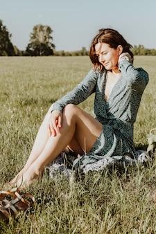 Plenerowy moda portret piękno młoda kobieta w bławym smokingowym obsiadaniu na zielonej trawie. letnia odzież i akcesoria.