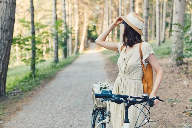 Plenerowy portret atrakcyjna młoda brunetka w kapeluszu na bicyklu.