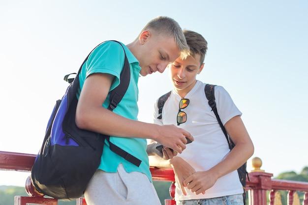 Plenerowy portret dwa mówiących nastolatków nastolatków