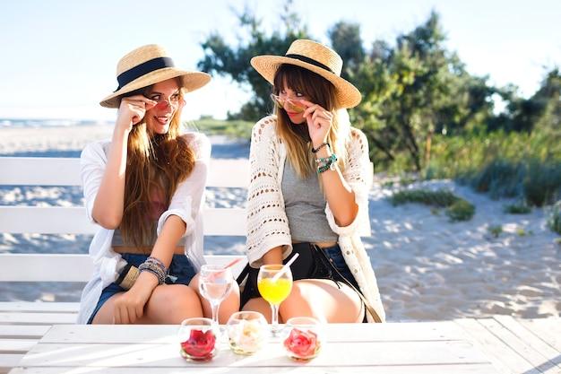 Plenerowy portret dwie siostry bijące przyjaciółkę, która dobrze się bawi, ściska uśmiechając się i robiąc grymasy na barze na plaży, ubrania w stylu boho hipster, pije smaczne koktajle, letnie wakacje nad oceanem.