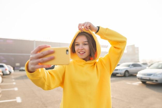 Plenerowy portret elegancka kobieta w ulicznych ubraniach robi selfie.