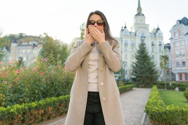 Plenerowy portret młoda kobieta zakrywa jej usta z rękami